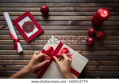 Image of female hands tying knot on giftbox surrounded by Christmas symbols - stock photo
