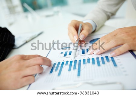 Image of female hands with pens over business document at meeting - stock photo