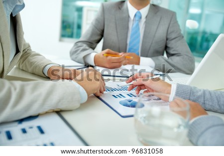 Image of female hands with pens over business document on background of their boss - stock photo