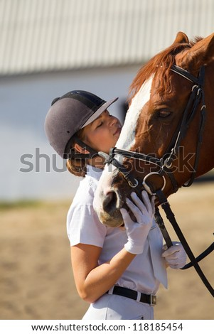 Image of  female jockey with purebred horse outdoors