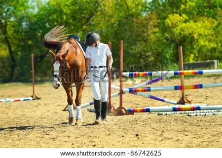Image of  female jockey with purebred horse outdoors - stock photo