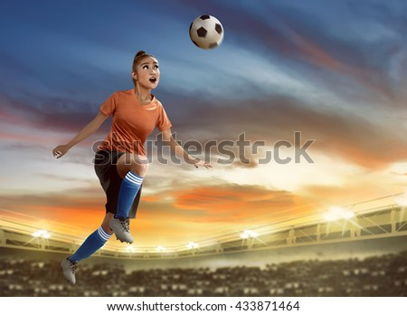 Image of female soccer player heading ball on the field - stock photo