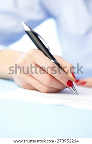 Image of female student sitting at desk and writing her presentation.
