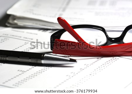 Image of financial report with pen and reading glasses at the office