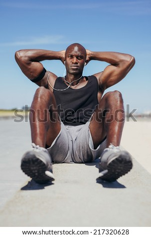 Image of fit young man doing sit-ups looking at camera. African fitness model exercising outdoors. - stock photo