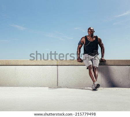 Image of fit young man relaxing on embankment after his run against blue sky. African male athlete outdoors with copyspace. - stock photo