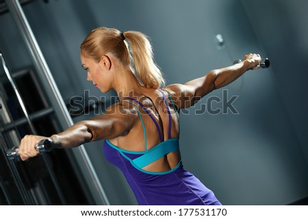 Image of fitness girl in gym exercising with dumbbells