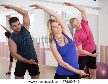 Image of fitness group stretching trunk after workout - stock photo