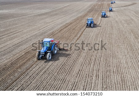 Image of five Tractors planting farm fields - stock photo