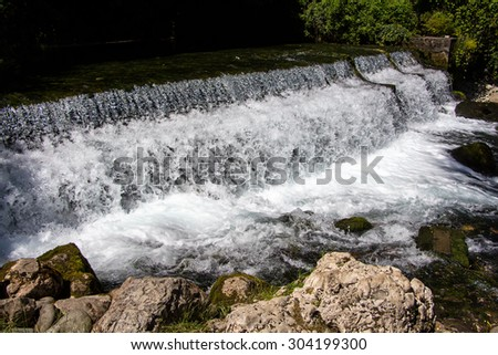 Image of foaming flowing water among stones, summer