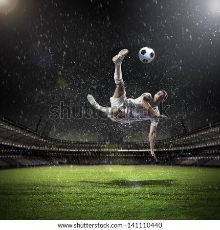 Image of football player at stadium hitting ball - stock photo