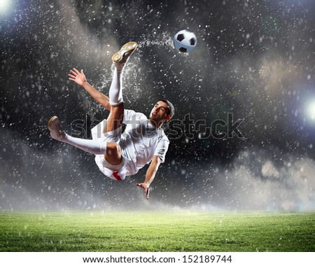 Image of football player at stadium hitting ball - stock photo