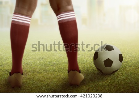 Image of football player feet with ball on the field - stock photo