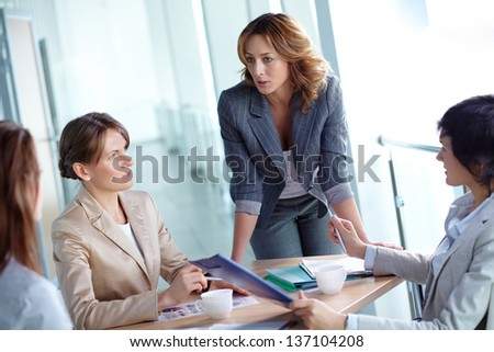 Image of four businesswomen discussing business plan at meeting - stock photo
