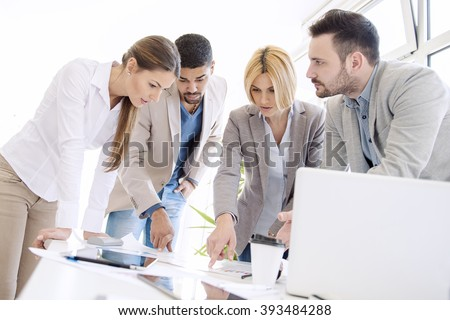 Image of four successful business partners working at meeting in office
