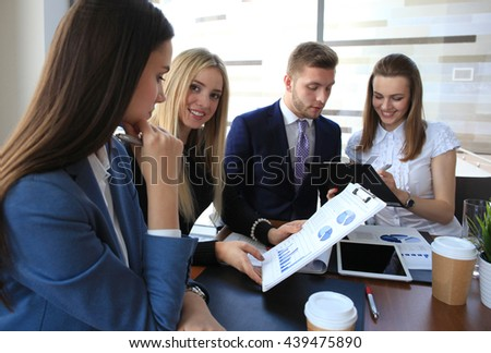 Image of four successful businesswomen looking at camera at meeting - stock photo