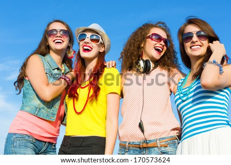 Image of four young attractive girls having fun outdoors