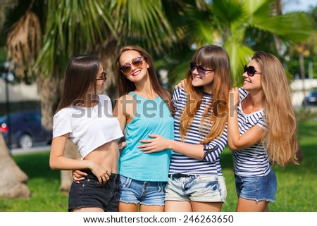 Image of four young attractive girls having fun outdoors. Group Of Four Teenage Girls  In summer Park. four smiling student girls studying in green park