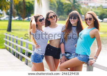Image of four young attractive girls having fun outdoors. Young and attractive girlfriends have fun in park. Four women n summer park - stock photo