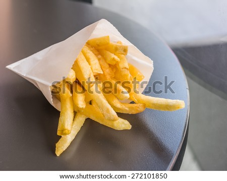 image of french fried on brown wooden table .