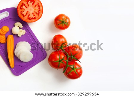 image of fresh tomatoes carrot onion and garlic , whole and sliced, on white background - stock photo