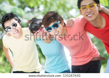 Image of friend's team embracing outdoors - stock photo