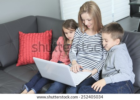 Image of friendly family sitting on the sofa and looking at laptop - stock photo