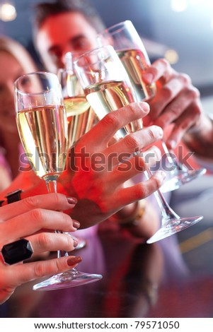 Image of friends hands holding crystal glasses full of champagne