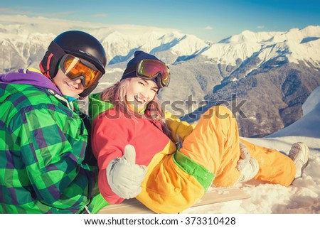 Image of funny couple of young man and woman snowboarder, skier on the background of Alps summit, Swiss mountains. Fun! - stock photo