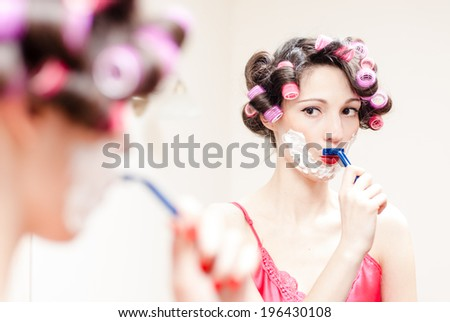 image of funny young beautiful pinup woman in pink curlers & shirt having fun shaving mustache with razor and foam on copy space background closeup portrait - stock photo