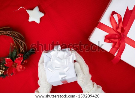 Image of giftbox held by female in gloves surrounded by other xmas symbols