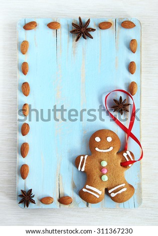 Image of Gingerbread man cookie on blue vintage cutting board with copyspace - stock photo