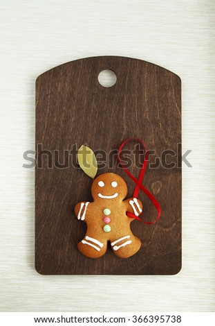 Image of Gingerbread man on brown cutting board with copyspace - stock photo