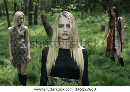 image of  girls posing in the green woods, three girls in nature - stock photo