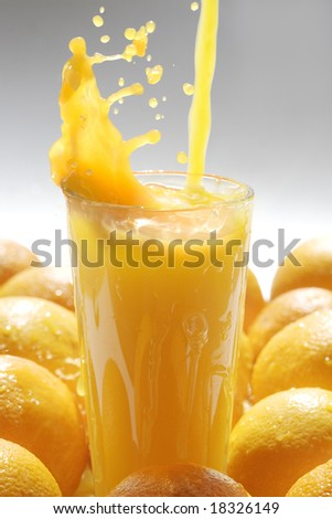 Image of glass of orange juice with fruits near by