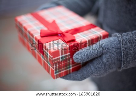 Image of gloved hand of guy holding box with Christmas present - stock photo