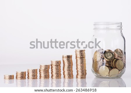 Image of Golden coins stacked and  penny jar over white background - stock photo