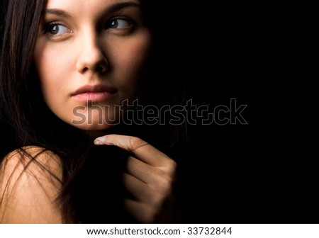 Image of gorgeous lady with dark hair touching it by hand and looking aside - stock photo