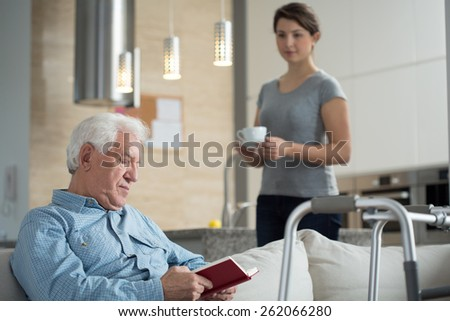 Image of granddaughter helping her disabled grandpa - stock photo