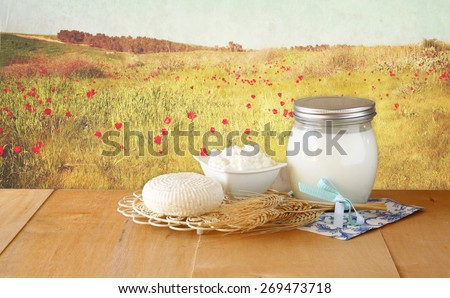 image of greek cheese , bulgarian cheese and milk on wooden table over floral abstract background. Symbols of jewish holiday - Shavuot  - stock photo