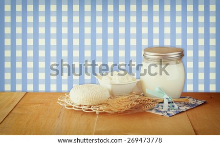 image of greek cheese , bulgarian cheese and milk on wooden table over vintage rustic background. Symbols of jewish holiday - Shavuot  - stock photo