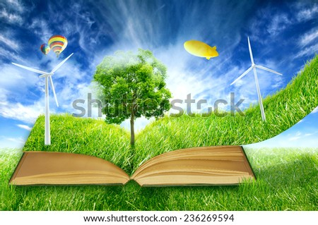 image of green micro world, book covered with green grass wind energy with turbines installed. Sustainable source of electricity, power supply concept. Eco environmentally friendly technology approach