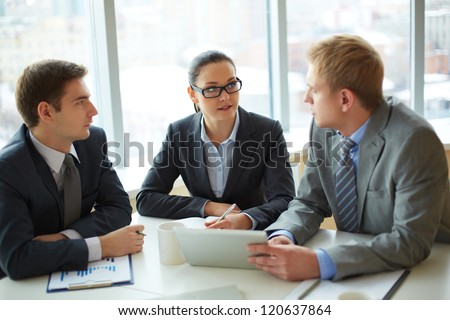 Image of group of employees discussing new ideas or project at meeting
