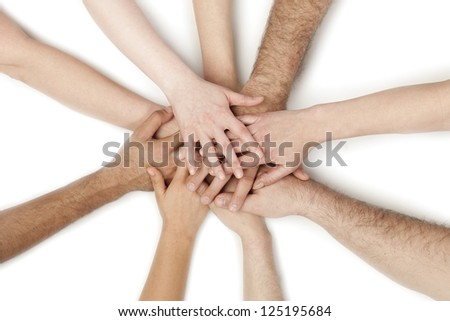 Image of group of overlapping hands against white background