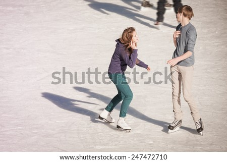 Image of group of teenagers holding hands on the ice skating at the Medeo