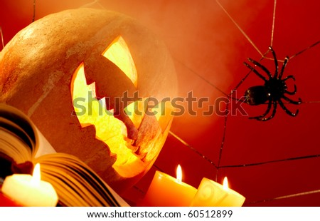 Image of Halloween pumpkin with burning candles and cobweb with spider near by - stock photo