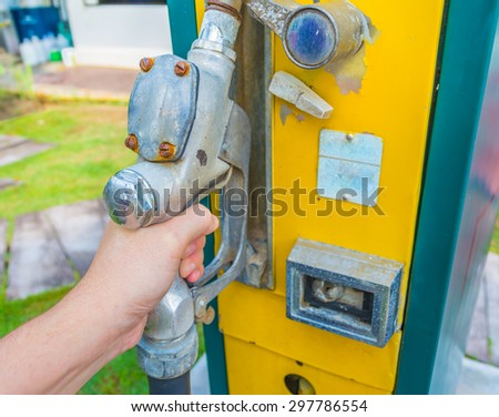image of hand holding the gasoline tap to Refuel the car on a gas retro oil station. - stock photo