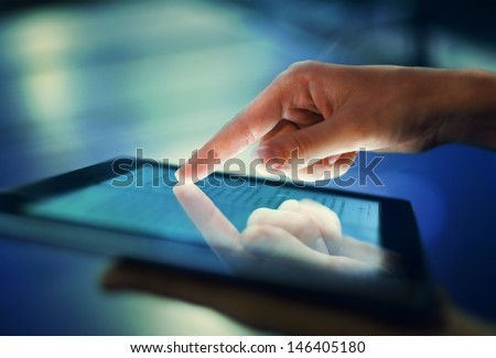 Image of hand pressing on screen digital tablet