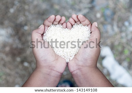 image of hand with rice in shape of love