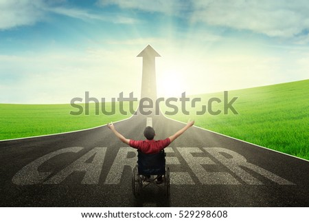 Image of handicapped man sitting on a wheelchair  and raising hands up on the road with career word while looking an upward arrow